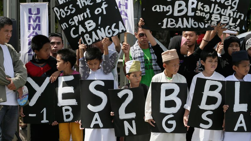 Filipino Muslims display placards during a rally at the Philippine Senate to coincide with the hearing at the Upper House on the passage of the Bangsamoro Basic Law (BBL) on Monday. President Aquino on Monday offered to discuss with senators their reservations about the proposed BBL, which swiftly hurdled a House committee after a meeting with him in Malacañang.  AP PHOTO/BULLIT MARQUEZ