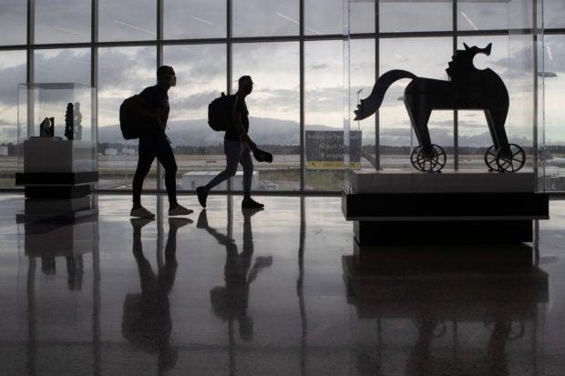 Passengers walk past artwork between terminals at IAH George Bush Intercontinental Airport amid the coronavirus disease (COVID-19) outbreak in Houston, Texas, U.S., July 21, 2020. REUTERS/Adrees Latif